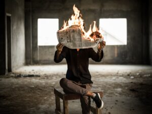 image description. A man reading burning newspapers representing access to low quality environmental information.